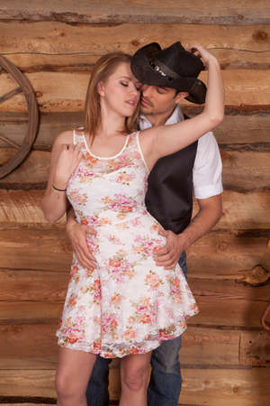 A western couple is standing together and she is holding his hat.