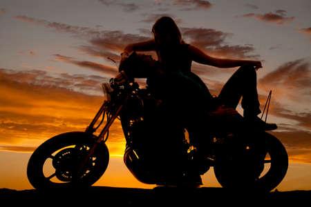 parejas de amor: Una silueta de un hombre que pone en una moto con una chica que pone sobre �l. Foto de archivo
