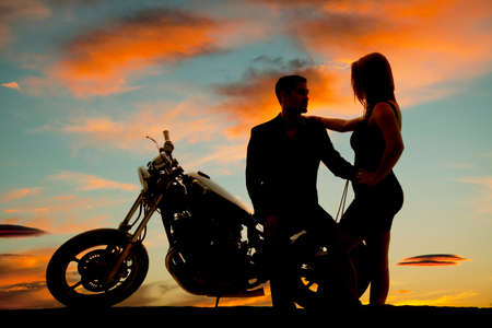 two men: A silhouette of a man sitting on his bike holding on to his woman.
