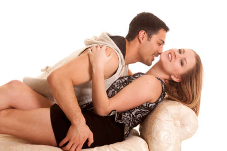 A man is laying by a woman with his face by her neck. photo