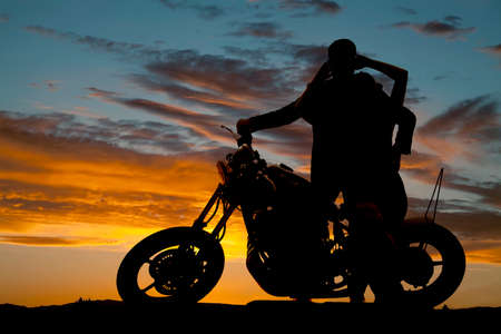 A silhouette of a man and woman next to a motorcycle holding each other. photo