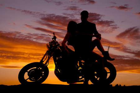 hombres guapos: Una silueta de una mujer sentada en una motocicleta a su hombre est� mirando hacia abajo en ella. Foto de archivo