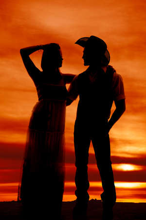 a silhouette of a woman looking into her cowboys eyes. photo