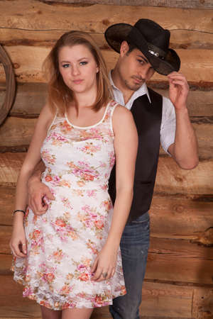 A cowboy holding on to his woman, he is touching the brim of his cowboy hat.
