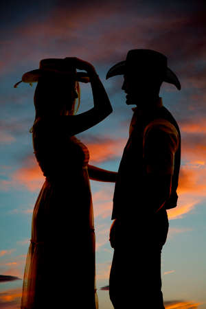 A silhouette of a woman in her cowgirl hat looking at her cowboy. photo