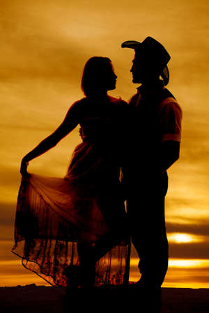 A silhouette of a woman holding out her dress with her cowboy looking at her. photo