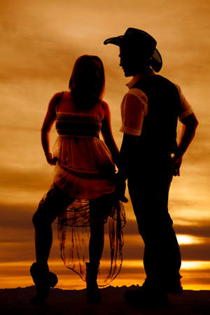 a silhouette of a woman holding up her dress looking at her cowboy. photo