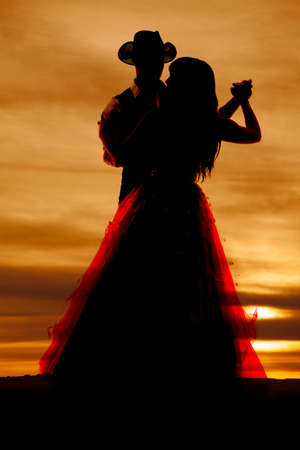 A western silhouette of a couple dancing together.