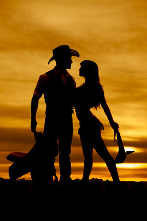 A silhouette of a cowboy and an indian in front of a sunset. photo