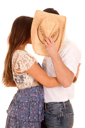 A close up of a cowboy kissing a girl behind his hat. photo