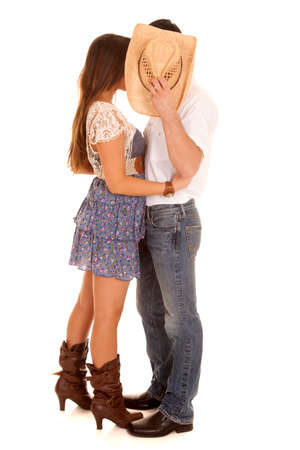 A country couple is kissing behind a cowboy hat.