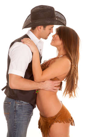 A cowboy and Indian couple are embracing and are about to kiss. photo