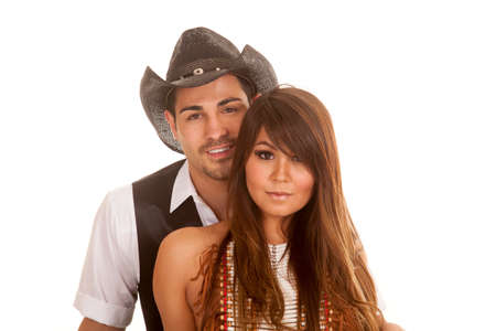 A cowboy and Indian couple have their heads close together. photo
