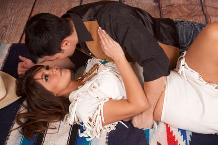 A cowboy and Indian are laying on a blanket about to kiss. photo