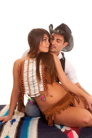 spanish ethnicity: A cowboy and Indian couple are sitting together on a blanket about to kiss.