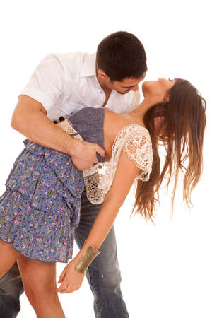 A man is dipping a woman in a blue dress with a white cardigan. photo