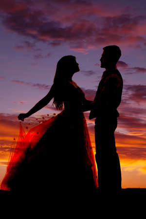 A silhouette of a western couple dancing in the light of the sunset. photo