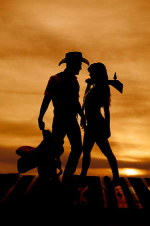A silhouette of a cowboy holding his saddle and an Indian holding her club. photo