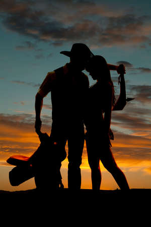 A western couple is standing in front of a sunset.  photo