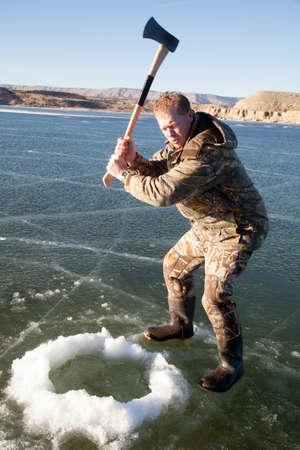 a man holding up his axe getting ready to chop more ice in his hole photo