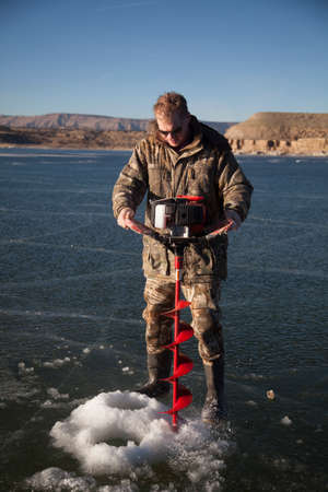 auger: A man using an ice auger to drill a hole in the ice. Stock Photo