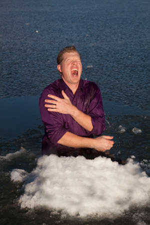 frozen lake: A man sitting in an ice hole with snow screaming.