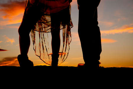 A silhouette of a woman's legs and her man next to her. She is holding up her dress. photo
