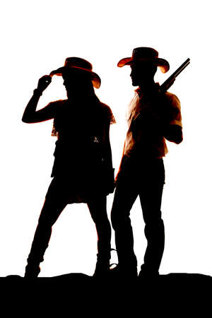 a silhouette of a cowgirl and a cowboy.  He is holding onto a gun. photo