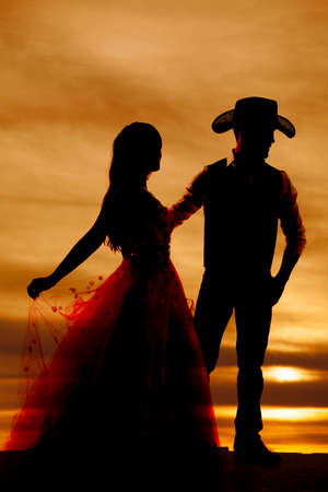 a silhouette of a cowboy holding onto his woman.