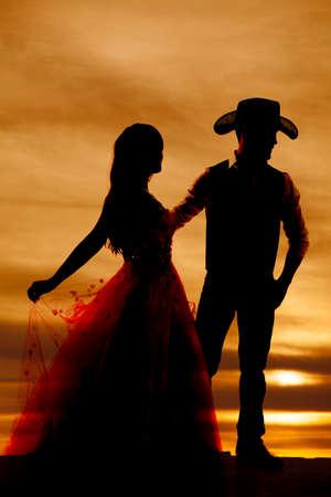Una silueta de un vaquero de sostener su mujer. Foto de archivo - 25125390