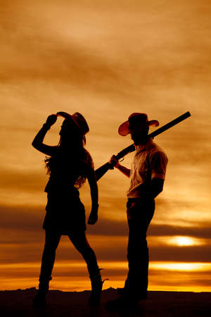 a silhouette of a cowgirl holding her hat while the cowboy is holding onto a gun. photo