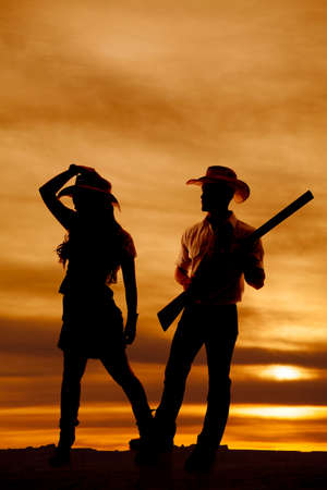 A silhouette of a cowgirl and cowboy in the outdoors. photo