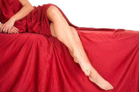 Legs of a woman with a red sheet on a bed with her arms showing also. photo