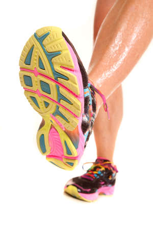 Legs of a woman running showing bottom of shoe. photo