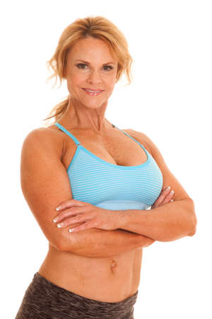 An older woman in a sports bra folding her arms. Stock Photo