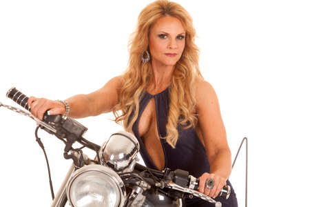 A mature woman is sitting on a motorcycle looking. Stock Photo