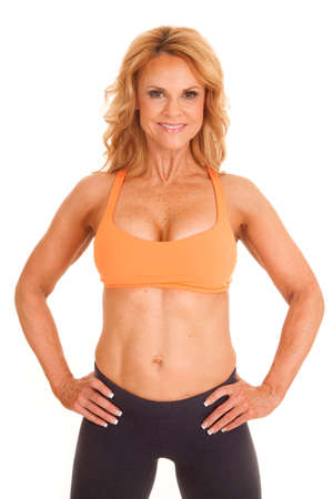 A woman in an orange sports bra with her hands on her hips. Stock Photo