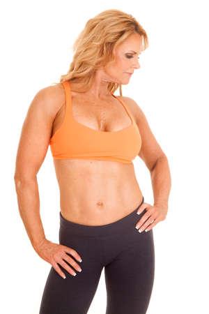 A mature woman in an orange sports bra standing. Stock Photo