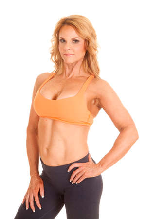 A woman in an orange sports bra with her hands on her hips. photo