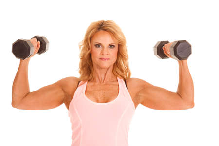 A woman in a pink tank with weights up flexing.
