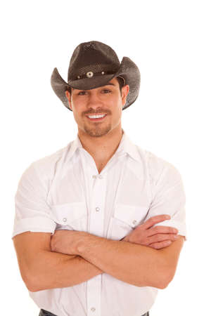 cowboy up: A cowboy in his western hat and shirt with his arms folded with a smile on his face.