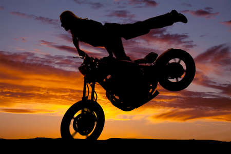 A woman on a motorcycle in the sunset silhouetted doing a stoppie with one leg up. photo