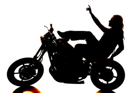 A silhouette of a woman sitting on a motorcycle with her hand in the air. photo