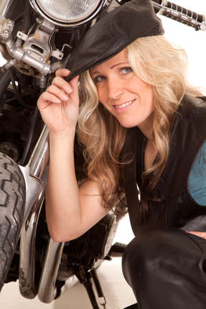 A woman in leather and a hat kneels by her motorcycle. photo