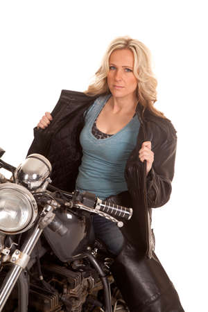 A woman in black leather sitting on a motorcycle holding her jacket open. photo