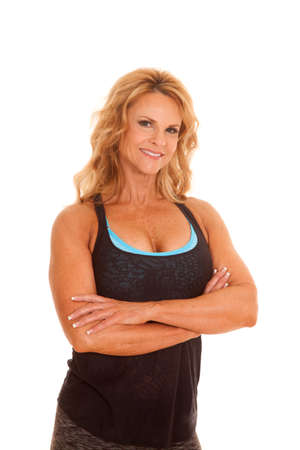 A woman in a black fitness top standing with her arms folded. photo