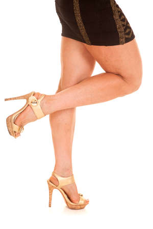 An older womans legs in heels in a skirt. photo