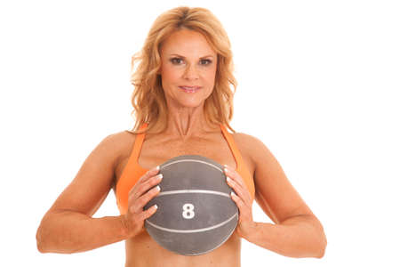 A woman in an orange sports bra holding a medicine ball. photo