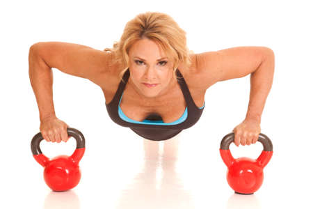 A mature woman doing pushups on kettle bells. photo