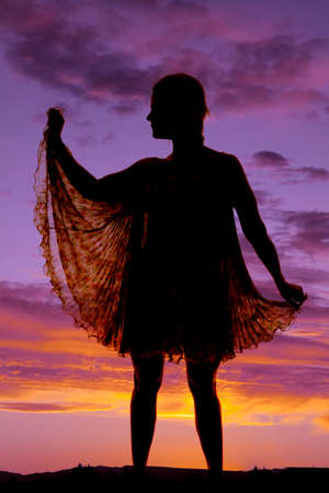 A woman is silhouetted in a see through dress in the sunset. photo